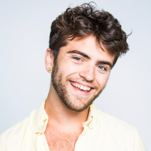 Dylan smiles against a white backdrop