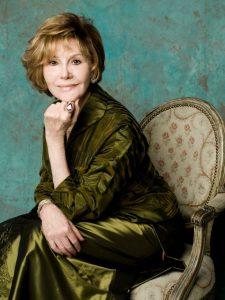 Photo of Glorya Kaufman sitting on a chair wearing a green dress