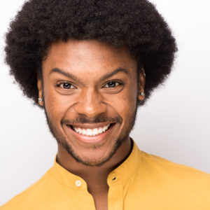 Jakevis Thomason smiling wearing a yellow shirt