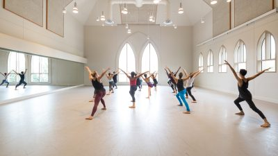 dance students with their backs facing the camera and arms up in a V