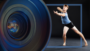 Video Stage camera and dancer wearing a blue shirt and black shorts reaching his arm out