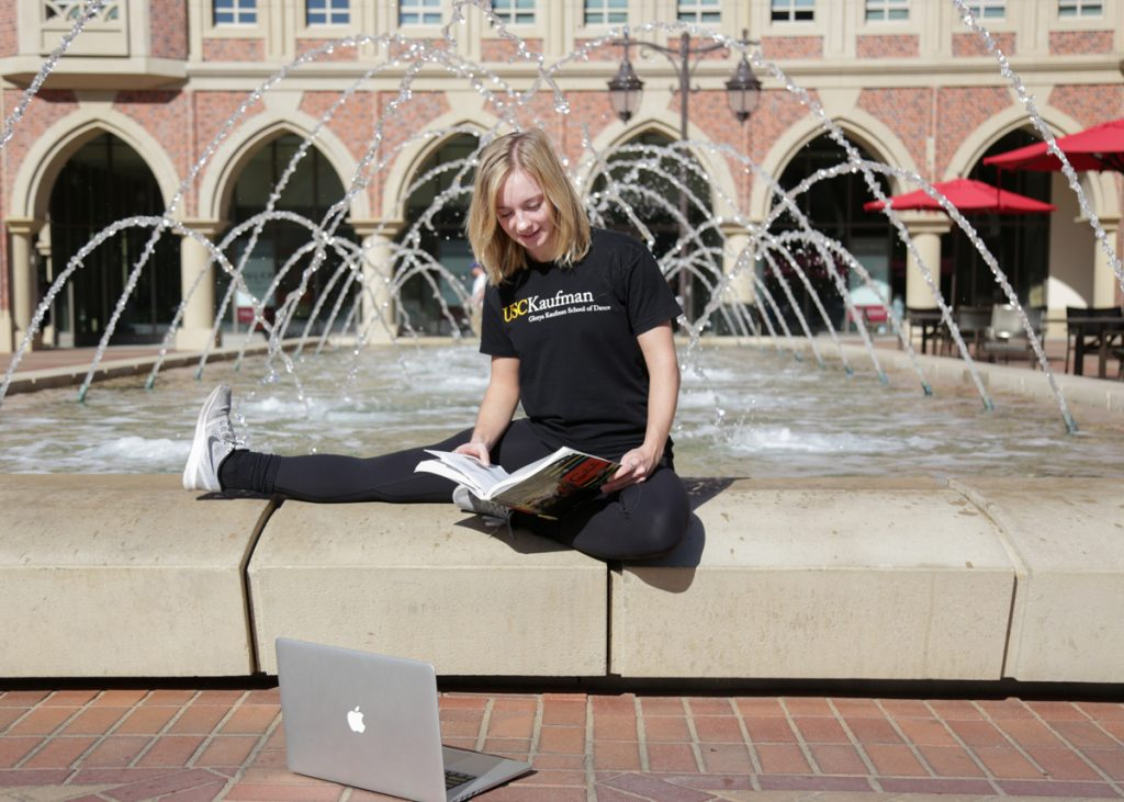 Girl sitting outside studying in front of fountain.