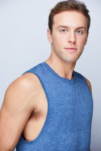 close up of a guy with short blonde hair wearing a blue tank
