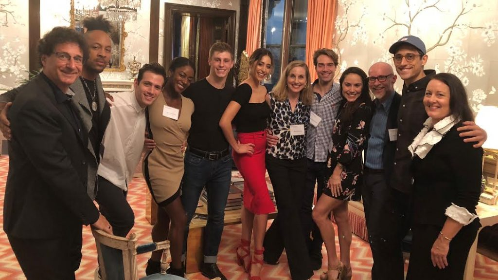 USC Kaufman students and faculty pose with guests in a dining room.