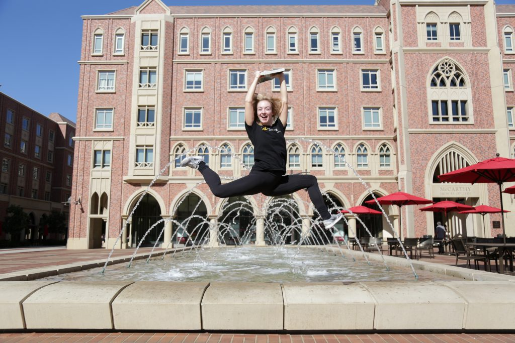 Girl jumps with her arms in the air in front of a water feature in the USC Village