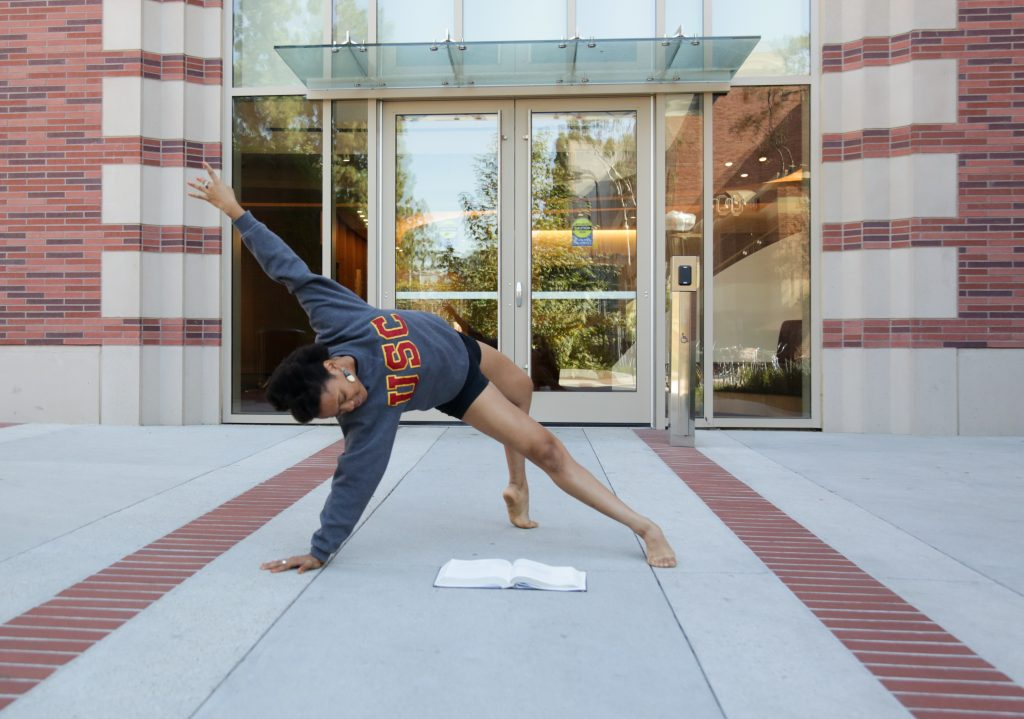 A female dancer strikes a pose as she reads a text book in front of the Glorya Kaufman Dance Center