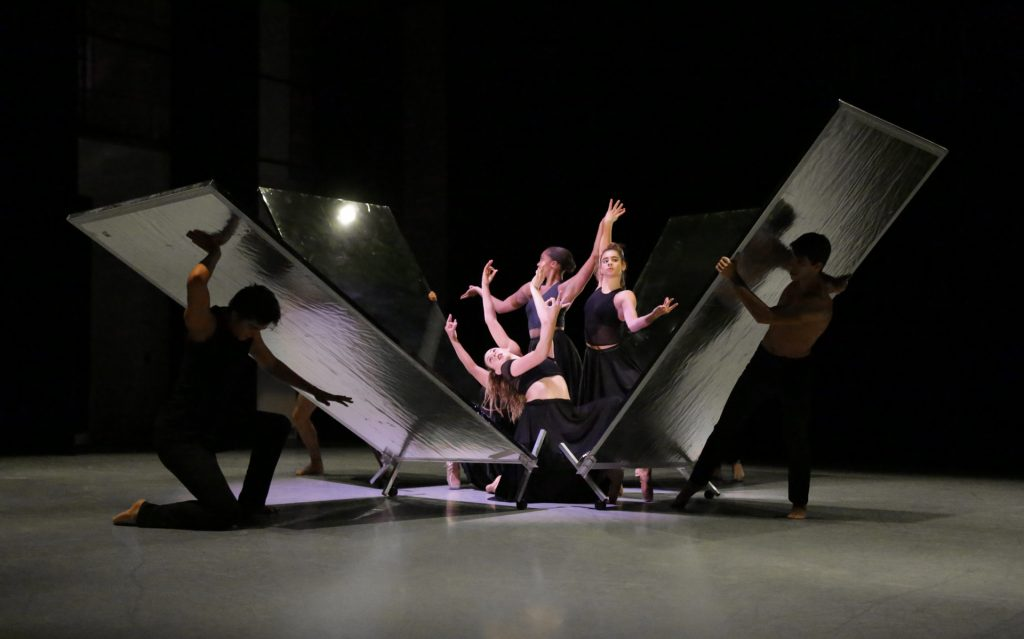 Dancers hold angular poses as a box of mirrors is dismantled around them.