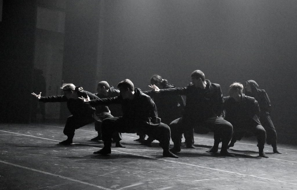 Dancers in all black on a dark stage.
