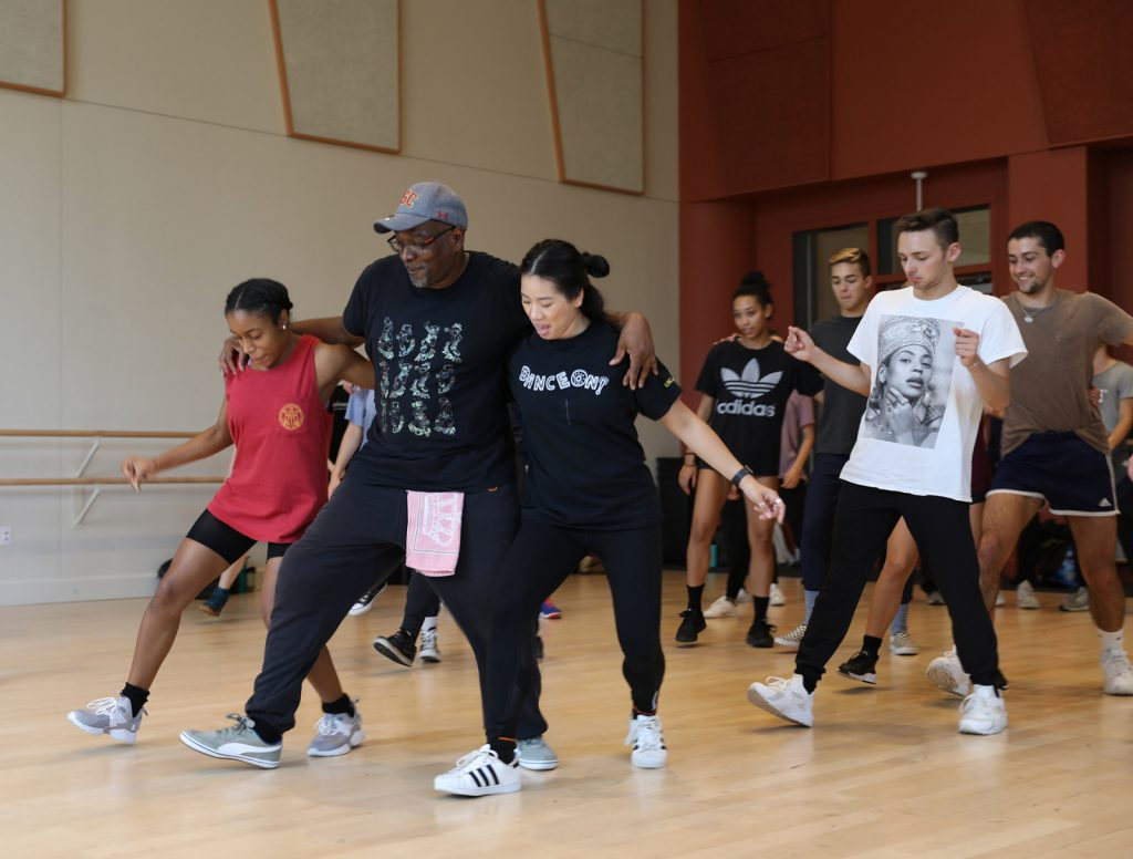 Teacher with his arms around two students as he teaches them dance steps in a studio.