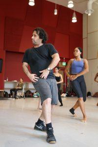 Man demonstrating dance steps in front of dance students in studio.