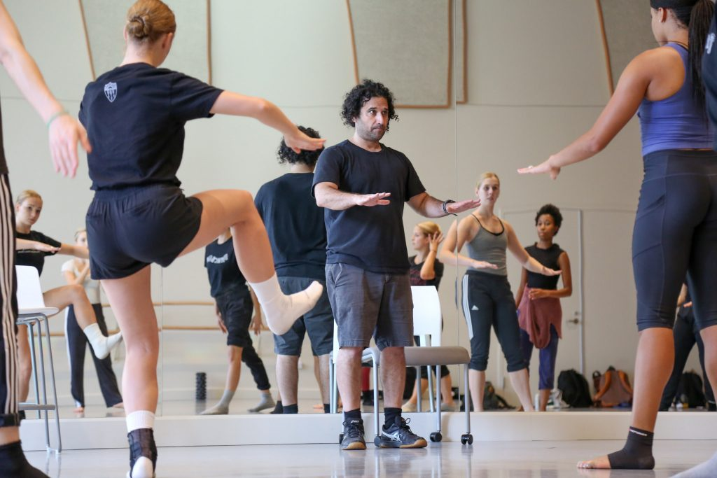 Man demonstrating hand gesture for dance students.