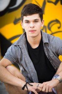 A portrait of a boy sitting in front of a yellow graffitied walll.