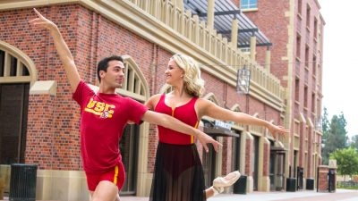 Man and woman in red and yellow dance attire outside at USC Village.
