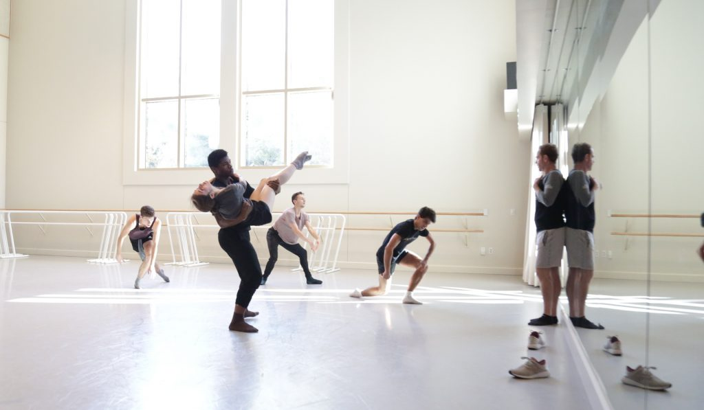Dancers in a studio with choreographer at the front, directing.