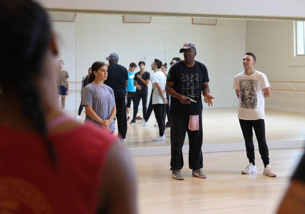Teacher talking to students in dance studio.