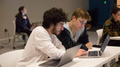 Two students at a desk looking at laptops