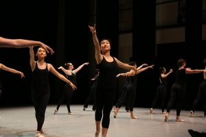 ballet students on stage wearing black tanks and tights