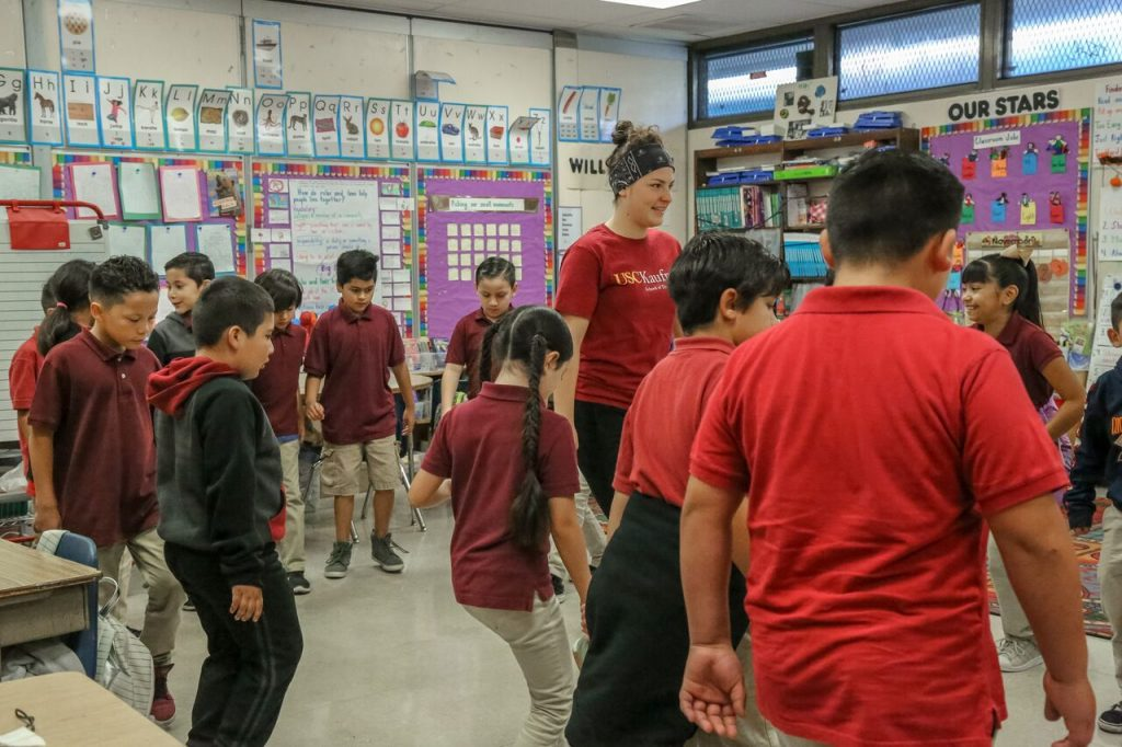 A female college student in a USC Kaufman shirts stands in the middle of a group of elementary schoolers as they dance in the classroom