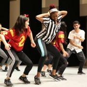 Students in sports jerseys perform at a hip-hop showcase.