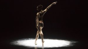woman in pointe shoes standing in spotlight with right arm up