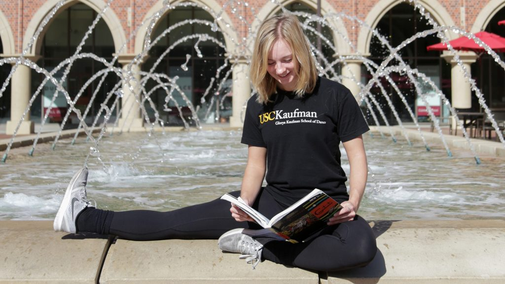 Woman sitting in front of a fountain reading a book