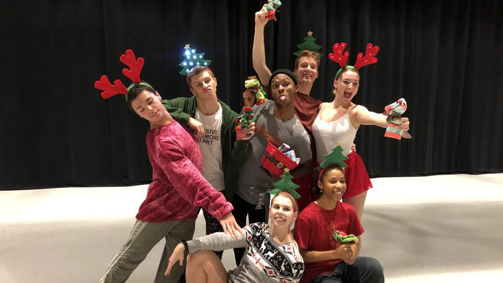 seven dancers pose wearing holiday-themed head bands