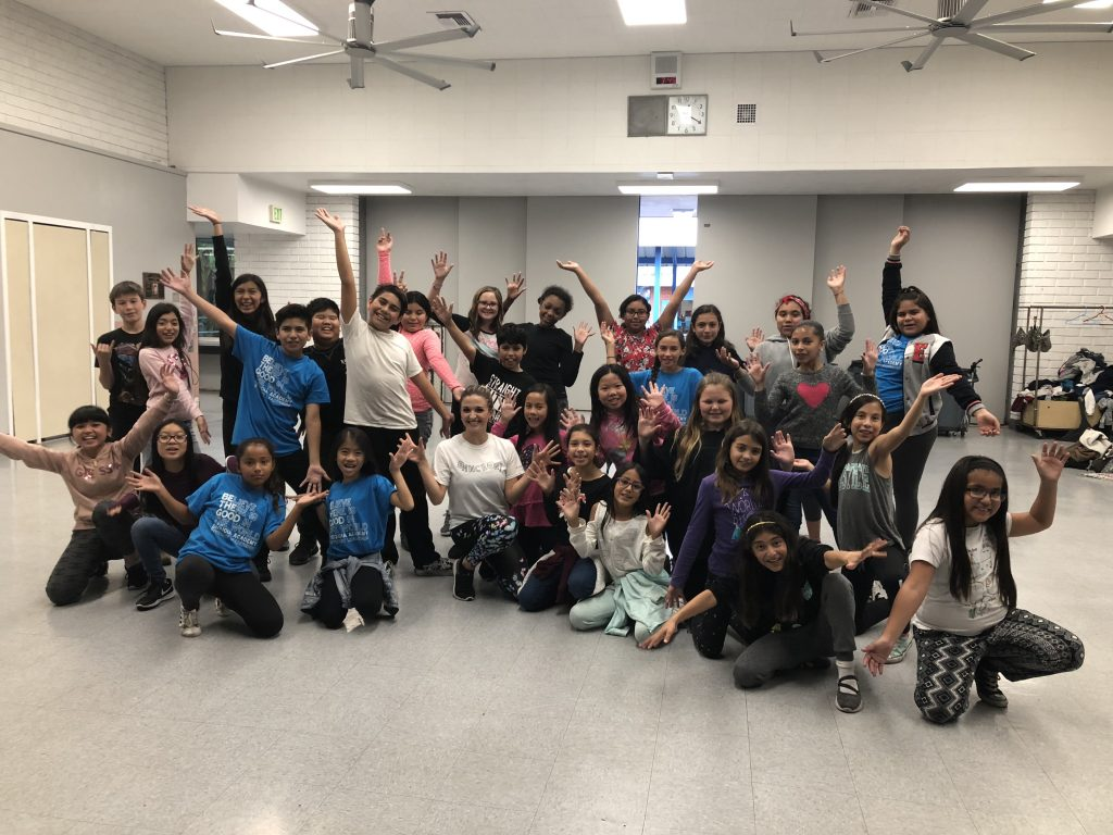 Jackie and her students pose in a group with their arms in the air