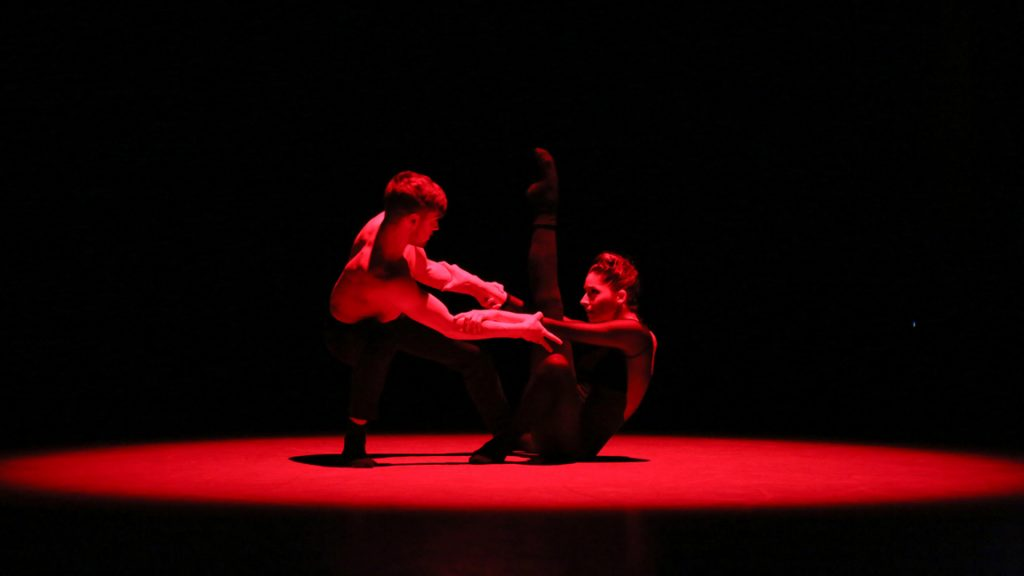 Man and woman dancing under red light.