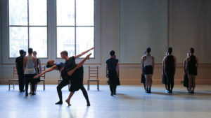 dancers rehearsing in a studio with tall windows