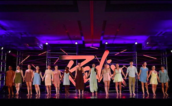 Young dancers holding hands on stage at dance convention