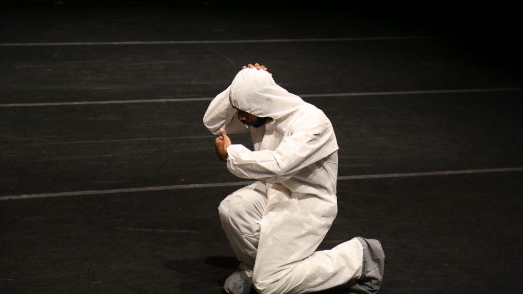man kneeling in white hazmat suit