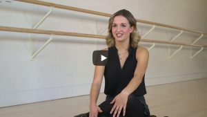 Woman sitting crossed leg on dance studio floor with play button