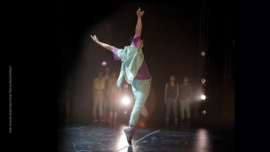 male dancer with arms up and standing on top of right toe