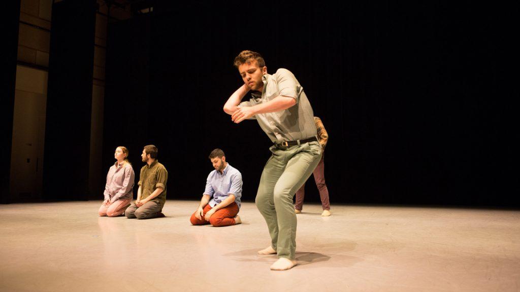 Dancers kneeling behind soloist
