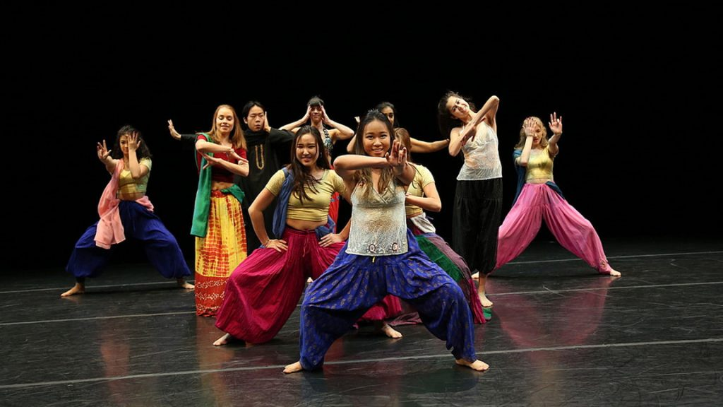 Dancers in brightly colored pants hitting a pose onstage