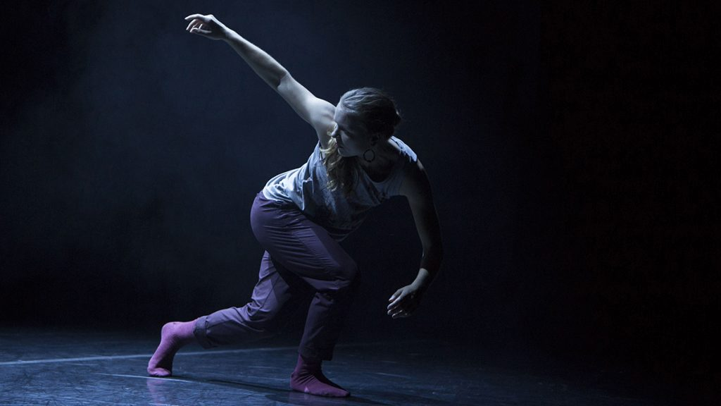 female dancer looking to her right with her right arm up