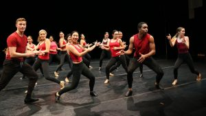 dancers wearing red tops and black bottoms on black stage