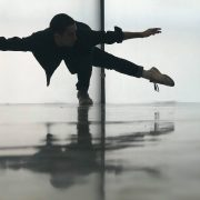 boy dancing in front of opaque window