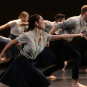 dancers in blue and gray clothing reaching forward on profile