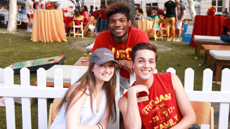 3 students in USC apparel smile
