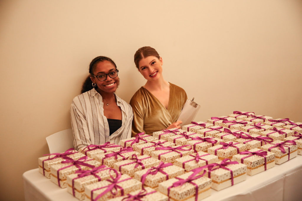 two women sitting behind table with gift boxes