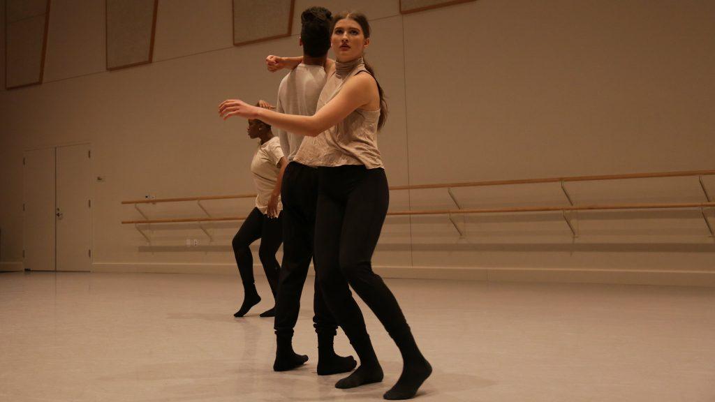 dancers wearing black pants and light tops in studio
