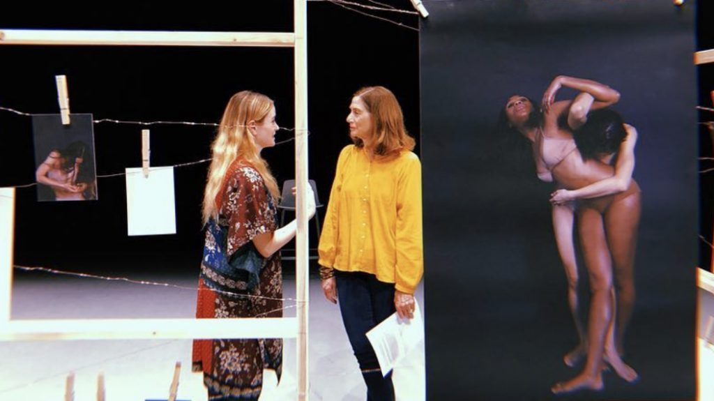 two women speaking surrounded by dance photographs
