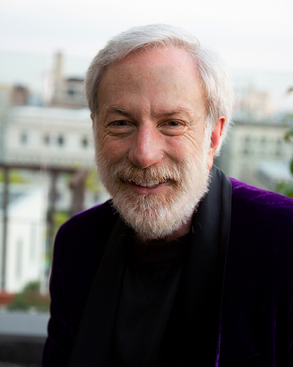 man with white hair and facial hair smiling and wearing a purple blazer