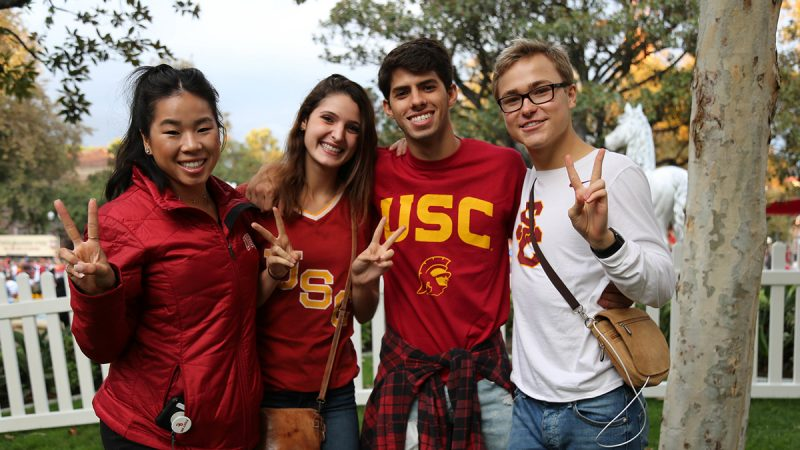 four college students wearing USC shirts smiling and giving the peace sign