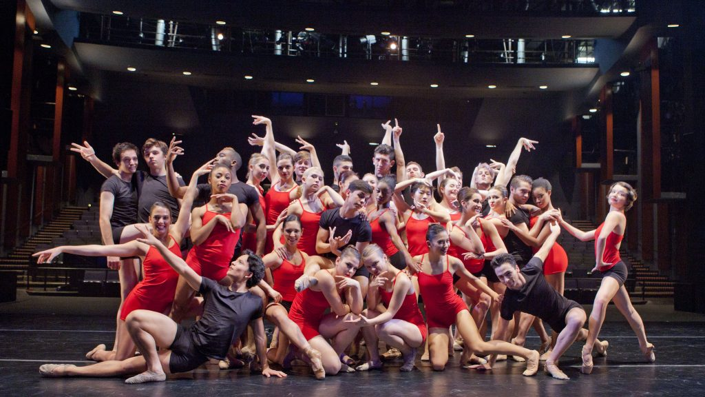 Many dancers in red and black posing onstage
