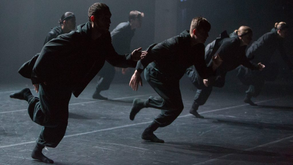 Dancers in all black running in a line onstage