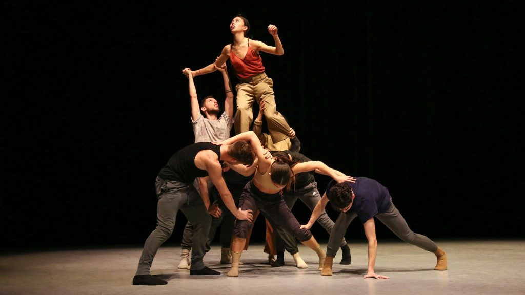 Dancers creating a structure with one dancer standing on top