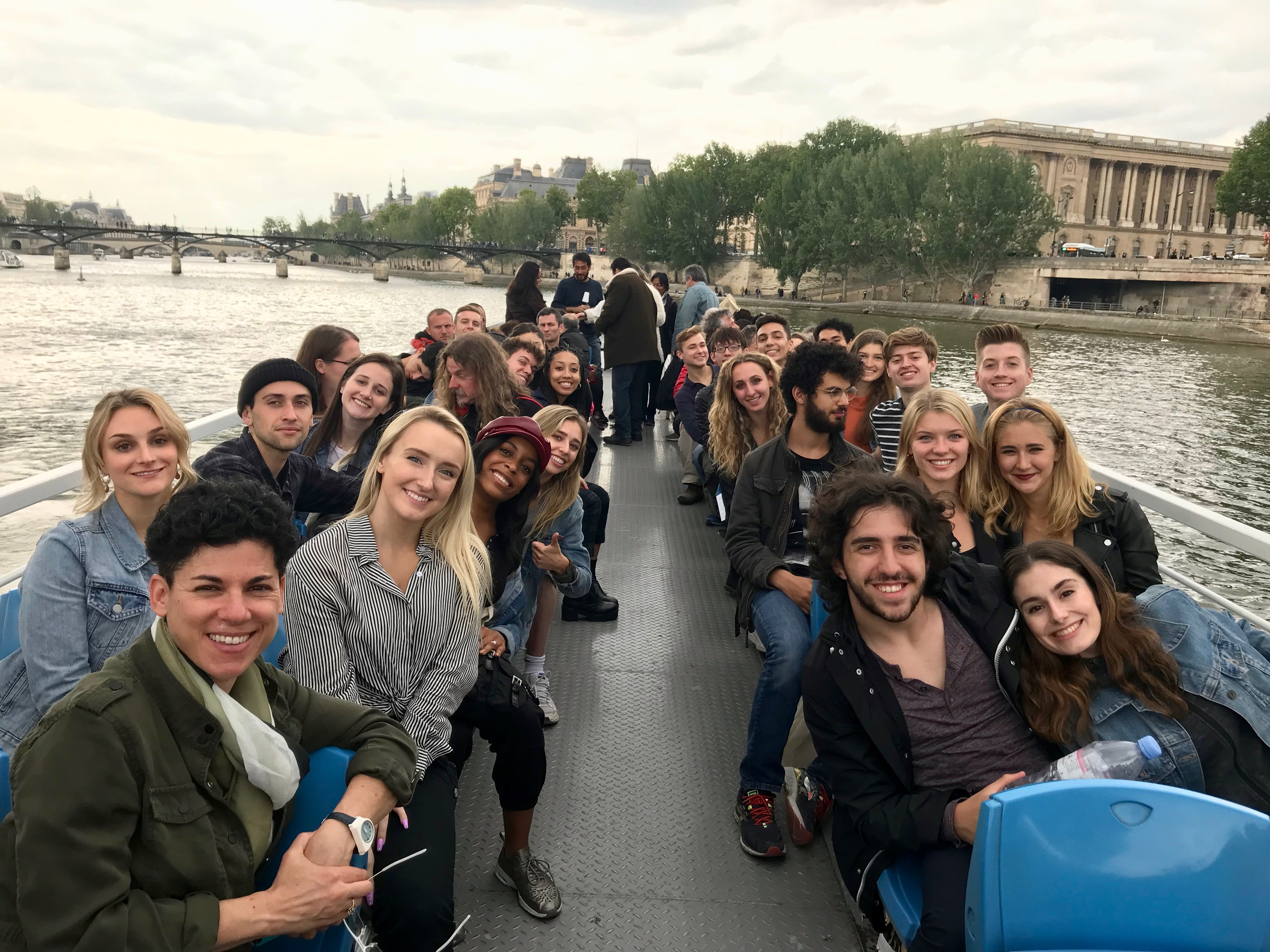 people smiling while sitting on top of tour boat