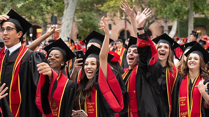 graduates wearing black caps and gowns with red sashes cheer and throw their hands up